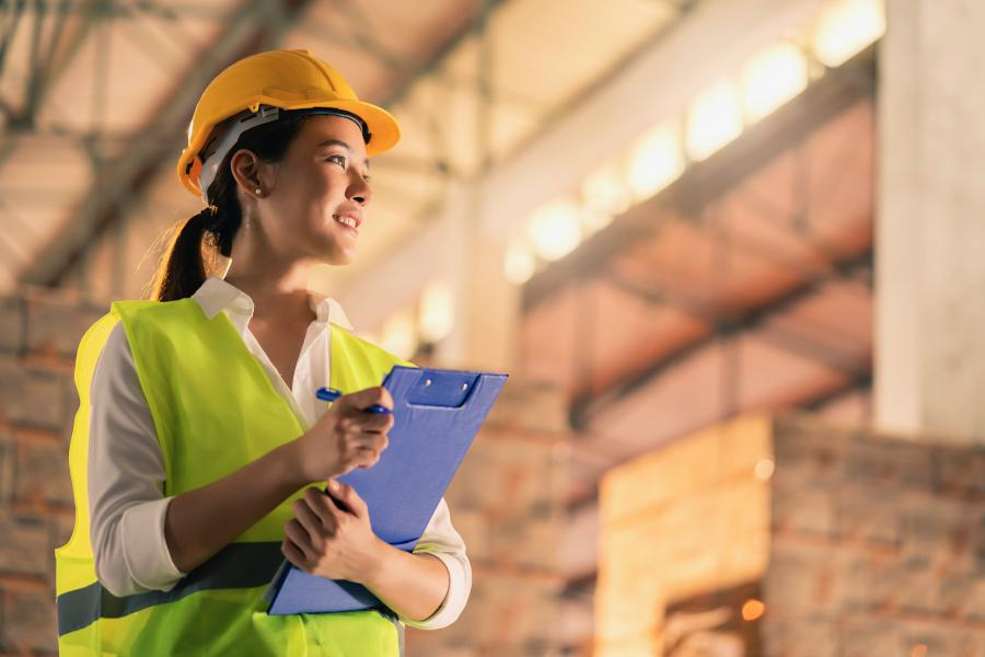 The image is of a young logistic worker surveying a warehouse