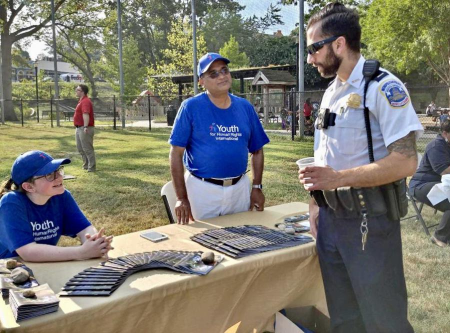 Volunteers discussing with DC Police Captain how human rights education can be used as a tool to combat human trafficking.