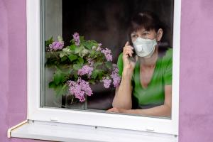 A sad lady wearing a face mask looks out of her window