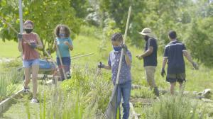 Several young adults and children holding rakes tend to ARECMA's garden.