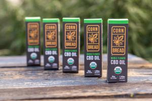 Five bottles of Cornbread Hemp's USDA certified organic Whole Flower CBD Oils in an organic hemp field.