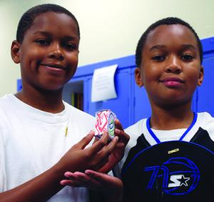 Students holding a box they designed using FabMaker engineering software and low-cost paper and card stock