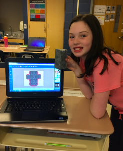 Girl student holds box she designed using the Engineering Design Process and FabMaker software to prototype her invention.