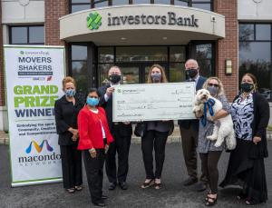 Seven people standing in front of an Investors Bank branch. Three people are holding a large check. On the left side is Movers & Shakers Small Busness Competition sign. On the far right a woman is hold a golden doodle dog, named Dash.
