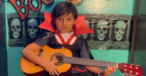 6 year old Jacob Marin plays the guitar in his vampire costume on his virtual stage.