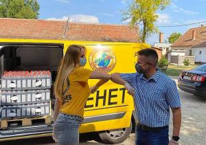 """Keeping the protocols in place, instead of shaking hands, a Volunteer Minister exchanges an """"elbow bump"""" with Csökmő Mayor Tibor Nagy who helps unload, divide up and bring supplies to at-risk families."""