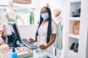 Joven comerciante afroamericana con una mascarilla médica que trabaja en una tienda de ropa.