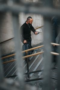 man walking up stairs, holding phone and backpack, listening to headphones in an outdoor city setting
