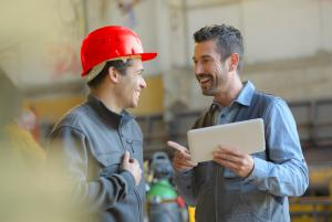 Two civil engineers talking and laughing with one holding a tablet.