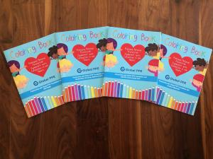 Four coloring books featuring a blue background, children pointing to a heart in the center, Global PPE's logo, and coloring pencils bordering the bottom, fanned out on a wooden surface.