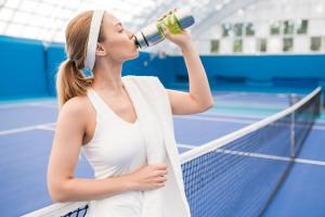 woman drinking water on tennis court