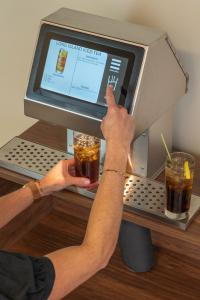 Bartender using Easybar Automated Cocktail Station to make a Long Island Iced Tea by selecting the drink on a touchscreen