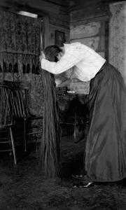 Photograph by Lora Webb Nichols of Mary Anderson brushing her long hair in a wood cabin in Encampent, Wyoming.