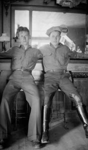 """Photograph by Lora Webb Nichols of """"Winters and McCarthy"""", two Civilian Conservation Corps Workers at Sugar Bowl Soda Foundation, Encampment, Wyoming, 1933, two men on barstools with arms around each other's shoulders"""