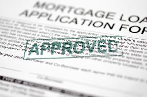 A green approved stamp on a mortgage application document