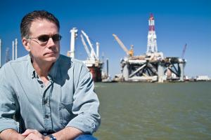 Man sat in front of oil rig