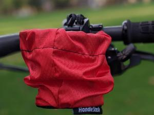 HandleStash cup holder in red color mounted to a bike handlebar
