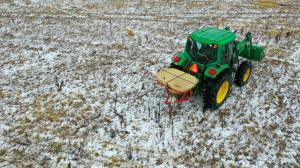 "alt=""Green tractor on snowy field spreads native seed mix containing seeds sourced from southern Illinois and Kentucky."""