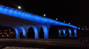 Photograph of the underside of the 35W Bridge over the Mississippi River in Minneapolis. The Bridge is illuminated in blue lights.