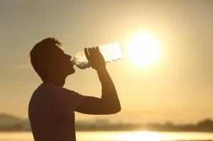 Employee hydrates himself to prevent heat illness while working during high temperatures