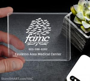A hand holding a clear plastic pocket, 3-inch by 4-inch. The pocket has a logo of a tree with the letter f a m c under it with a phone number.