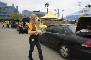 Los ministros voluntarios colocaron cajas de comida en los cofres de los autos que pasaban por el estacionamiento de la Iglesia de Scientology.