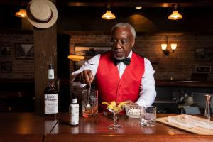 An actor as Tom Bullock guides visitors through Bourbon tastings in the Evan Williams Bourbon Experience speakeasy
