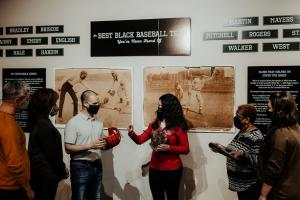Visitors are shown baseball artifacts from 1900 era Black players at the Louisville Slugger Museum and Factory