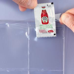 A hand is flipping open the top flap and inserting a ketchup packet.