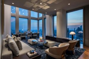 The space opens to an inviting and expansive area perfect for entertaining, with a double-story wall of windows and the beautiful city stretching beyond them.