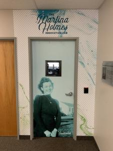 Image of the entrance to PetDine's Martina Holmes Innovation Lab with a black and white image of Martina Holmes covering the door.