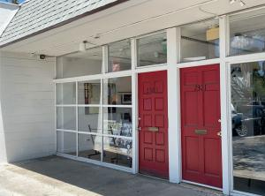 The image shows the front of the new gallery at 2323 Central Avenue with a red front door and glass facade.