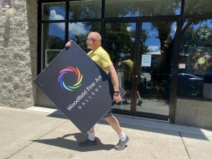 Photo of gallery owner and artist Jim Woodfield carrying his logo across the street to his new location.