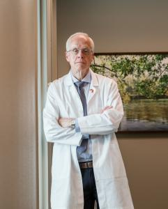 Dr. Bud Pierce, Republican Candidate for Oregon Governor at his office, learning against the wall,  in his white physican coat, light blue shirt, blue tie with white spots, picture of a creek inthe back. He has a serious look on his face.