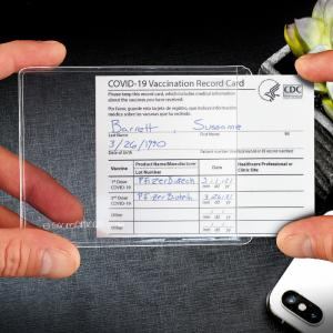 A vaccination card being slipped into a clear plastic pocket.