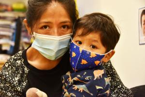 Mother and child with masks served by the Association to Benefit Children in New York