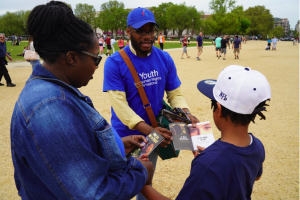 """Youth for Human Rights advocate distributing the """"What Are Human Rights?"""" booklets to parents and children"""